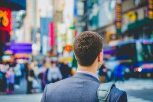 交差点に立って、前を向いているスーツ姿の男性